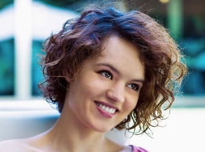 Curly young woman portrait, outdoors, close-up, positive attitude, smiling.